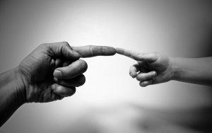 Een zwartwitte foto van een mannelijke hand en een vrouweljke hand, die zich verbinden door het aanraken van elkaars vinger, illustrerend faalangst kind.