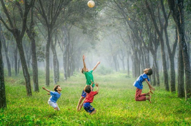 kinderen die samen aan het voetballen zijn in het bos en genieten van de sociale vaardigheden kind